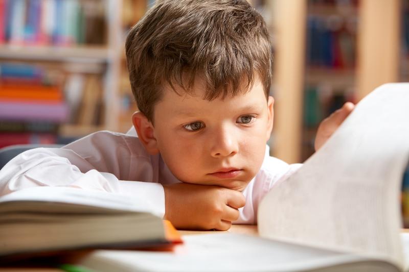 Ettertenksom gutt blar i skolebok