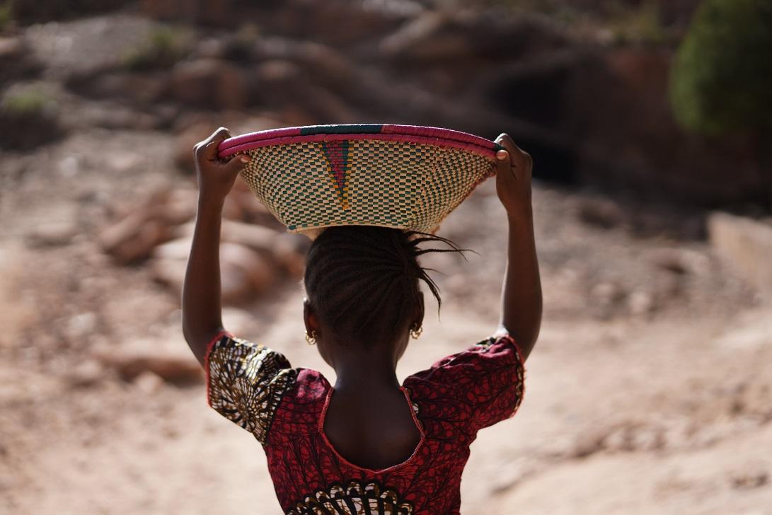 Ung afrikansk jente med kurv på hodet, sett bakfra.